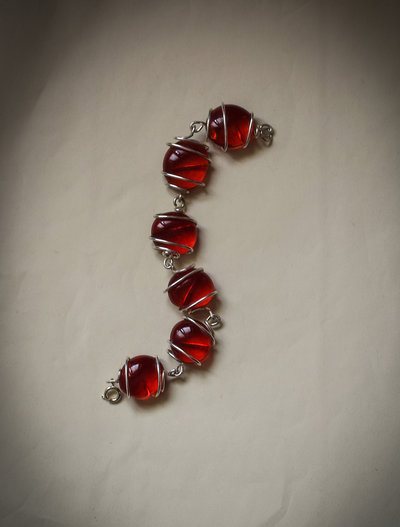 Bracciale perle vetro rosse incastonate su filo metallico argentato.