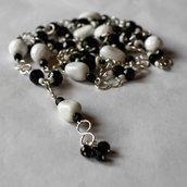 Collana doppia con pendenti in perle vetro sfaccettate e ovali, inserti metallici argentati.