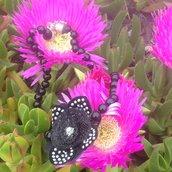 Collana in perle nere e fiore sintetico