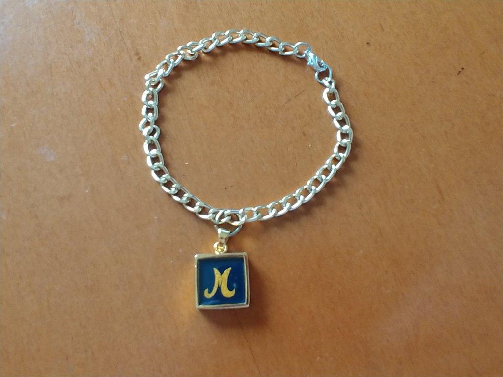 Braccialetto in metallo dorato e ciondolo con iniziale M di mamma su fondo nero.