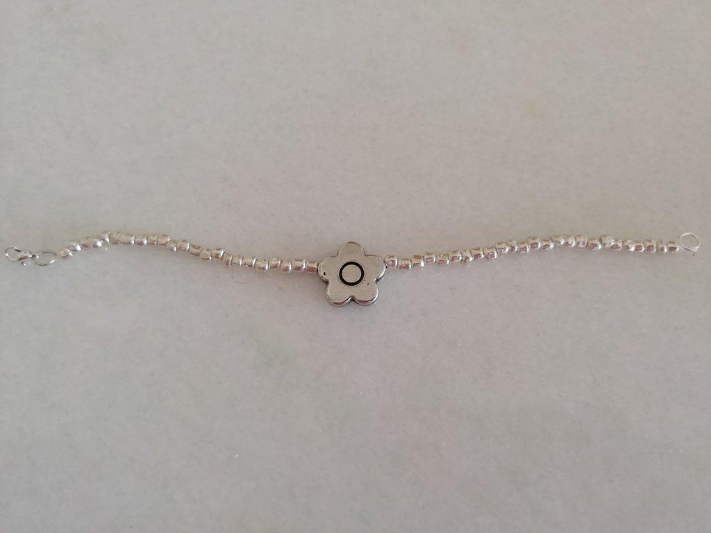 Delicato braccialetto realizzato con perline color argento e con fiorellino in acciaio
