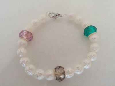 Braccialetto realizzato con perle bianche opache puntinate, con inserti in metallo e pietre colorate.Braccialetto realizzato con perle bianche opache puntinate, con inserti in metallo e pietre colorate.