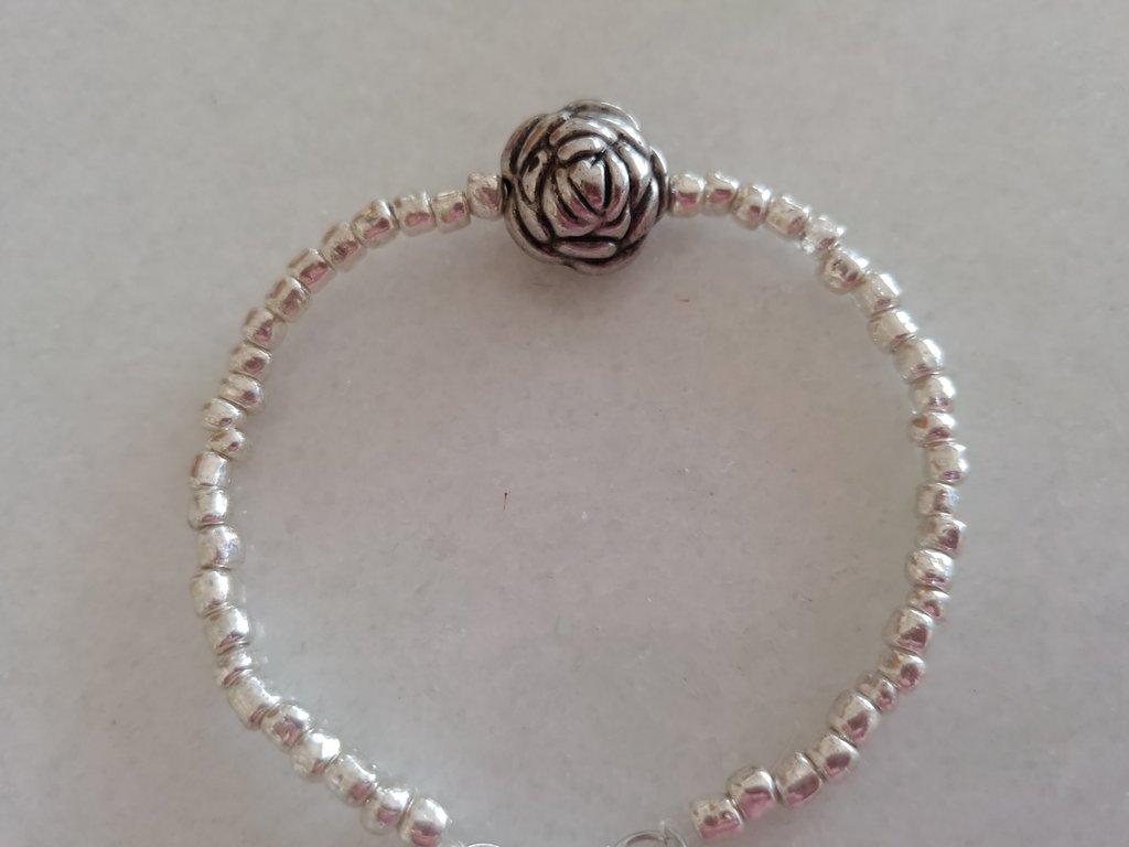 Braccialetto realizzato a mano con perline color argento con al centro  una graziosa rosa in metallo
