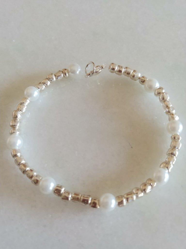 Braccialetto realizzato con perline color acciaio alternate da perle bianche.