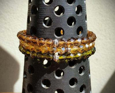 Tris bracciali in perle di vetro sfaccettate da 6 mm con intermezzo metallico, montate su filo elastico.