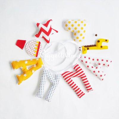 UNa ghirlanda rossa, gialla e blu con cuori, stelle, mongolfiere e giraffe per decorare la cameretta di Anna: un'idea regalo personalizzabile per festeggiare la sua nascita