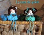 Bomboniere che rappresentano bamboline su fiore rosa, azzurro, giallo e verde
