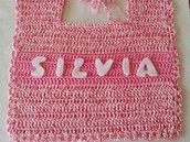 Bavaglino color fucsia sfumato realizzato a uncinetto con al centro il nome della bimba