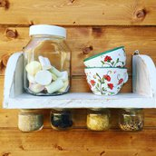 mensola bianca in legno con barattoli in vetro