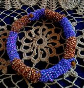 Braciale con fili di perline multicolore cucite a mano su cilindro senza chiusura nei colori viola e bronzo