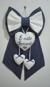 Fiocco nascita elegante con cuori in tessuto blu e bianco.