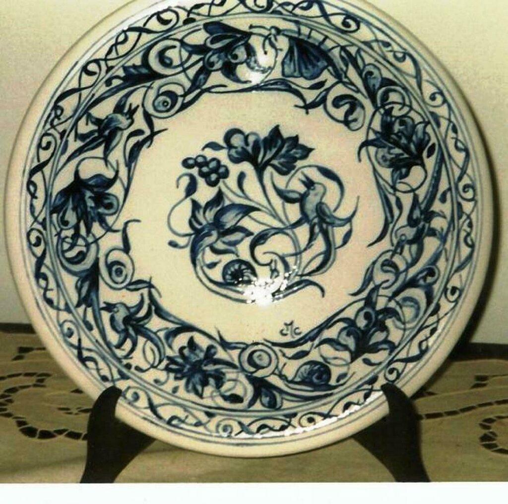 Piatto di maiolica dipinto a mano con varie sfumature di blu con motivo centrale e sulla falda di uccellino lumaca fiore e foglie