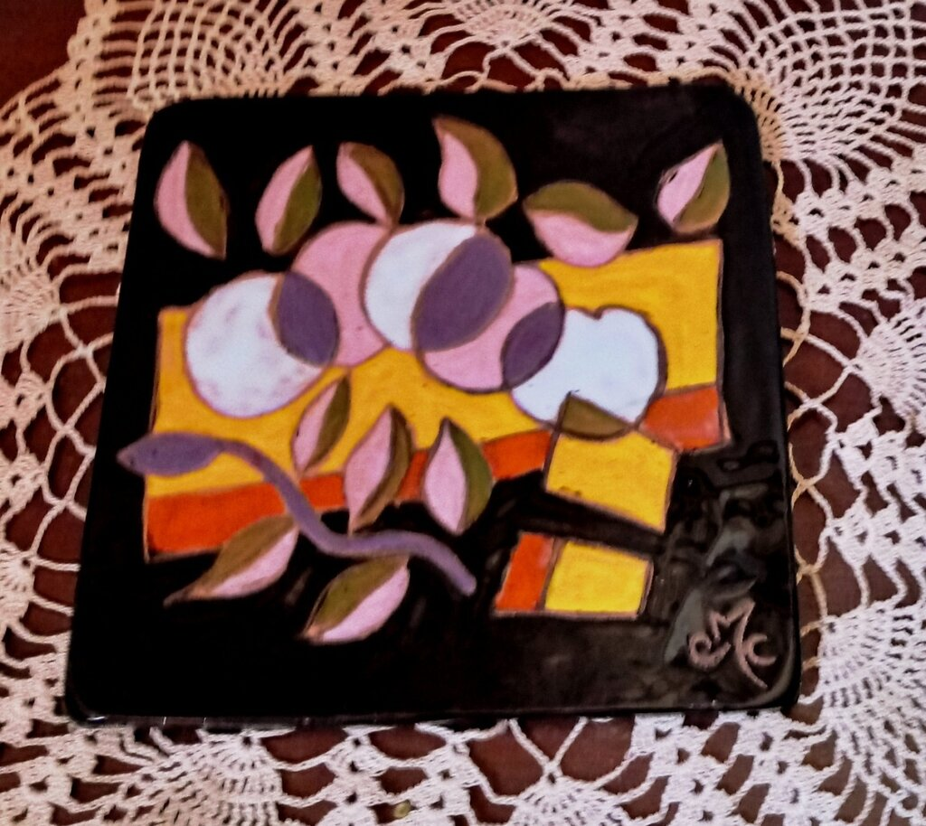 Piastrella sottopentola manufatta di ceramica dipinta con smalti su fondo nero disegno a colori vivaci di mele e foglie bicolori