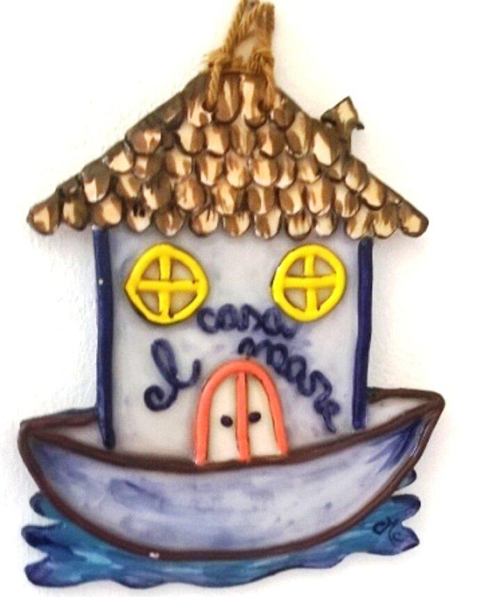 Casetta fuoriporta di ceramica da appendere, manufatta con elementi in rilievo poszionata su una barca dove si può scrivere il nome