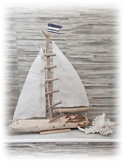 Barca a vela con legni di mare