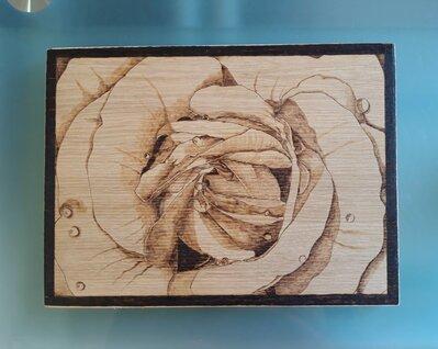 Quadretto con pirografia fatta a mano con un primo piano di una rosa