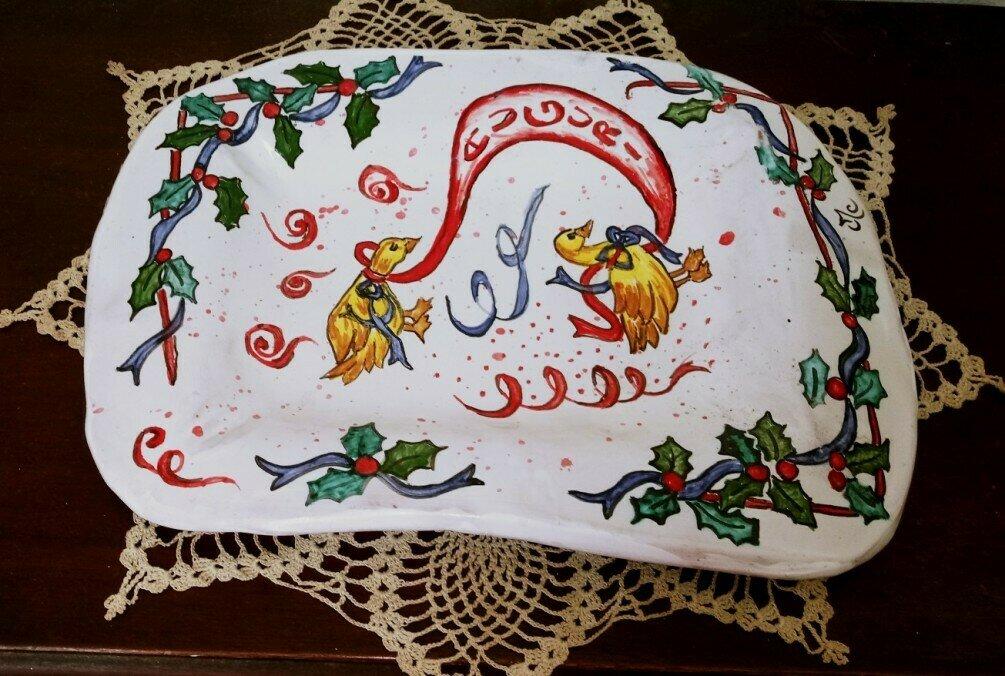 Vassoio di maiolica manufatto in creta rossa di forma rettangolare con bordi irregolari con falda, decoro con foglie di pungitopo con palline rosse e 2 oche che fanno gli auguri