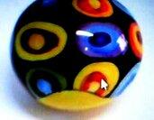 Pallina di Natale di ceramica dipinta a mano su un fondo nero tanti anelli multicolore per addobbare l'albero