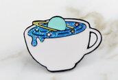 Spilla in metallo e smalto pianeta nella tazza