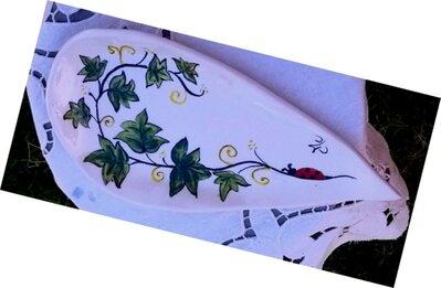 Poggia mestolo manufatto di ceramica dipinto a mano con tralcio con foglie di edera che termina con una coccinella