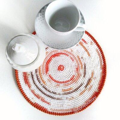 Centrino centrotavola lavorato all'uncinetto in cotone multicolore sui toni dell'arancione