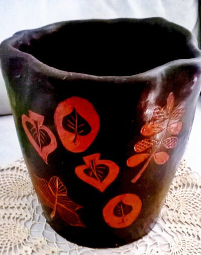 Vaso di ceramica lucidato a cera, maufatto di creta rossa su fondo nero motivi diversi  di foglie graffite che fanno risaltare il cotto sottostante