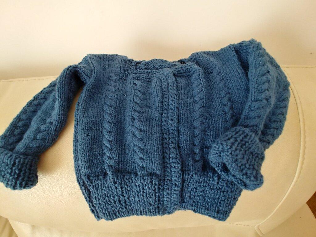 Giacchino da bimbo realizzato a ferri con filato di lana color blu acciaio. Impreziosito da treccine  sul davanti, sul dietro e sulle maniche