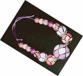 Collana manufatta di ceramica di media lunghezza formata da palline simmetriche di dametro diverso dipinte a mano con rombi di 2 colori