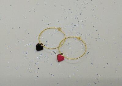 Orecchini a cerchio realizzati a mano di colore oro e pendenti cuore rosso e nero.