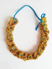 Collana cordone di passamaneria giallo senape intrecciato con altra passamaneria gialla che a sua volta risulta intrecciata con filo fettuccia turchese