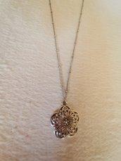 Catenina realizzata a mano in acciaio con piccole perline ogni 2 cm. Impreziosita da un pendente a forma di fiore con disegni molto grazioso