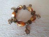Braccialetto elasticizzato, realizzato con pietre di colore senape e marrone sfumati,con distnziatori e ciondolini color bronzo.