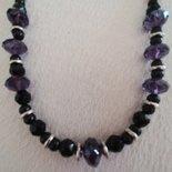 Elegante collana  realizzata a mano con perle nere tonde e sfaccettate alternate da pietre più grandi sfaccettate  di colore viola  con distanziatori formati da tondini di metallo e perle di color argento.