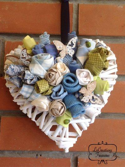 Cuore in midollino bianco con composizione di boccioli e fiori cuciti a mano