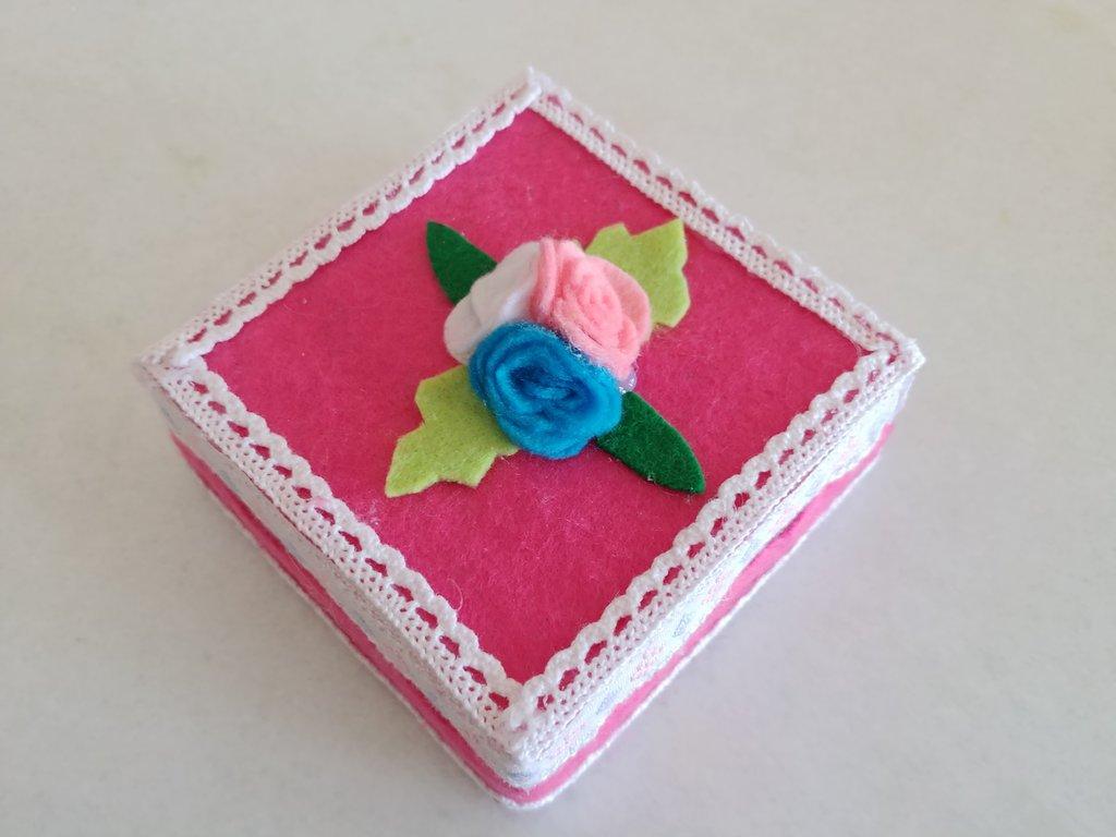 Portagioie quadrato rivestito da pannolenci color fucsia e impreziosito da roselline e merletto nel contorno.