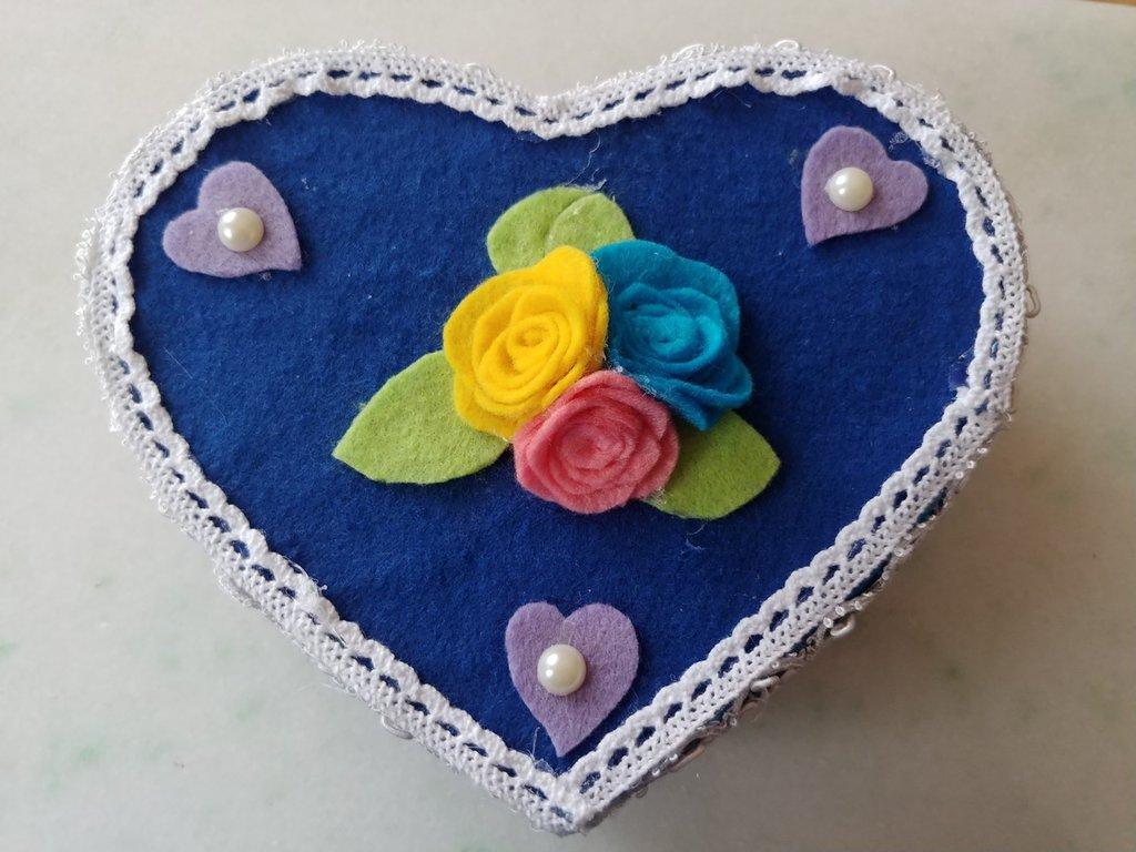 Portagioie a forma di cuore rivestito da pannolenci color blu e impreziosito da roselline e al centro e cuoricini color viola con perla al centro. tutto i lcontorno èrivestito da merletto macramè .