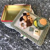Scatola di latta ricoperta di feltro con biscotti e tazza di the di feltro