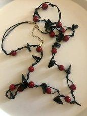Collana lunga con perle rosso scuro.