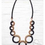 Collana ad anelli nero e oro a grandezza graduale, tecnica a crochet su legno e resina, filati lurex luminosi, inserti a foglia dorati