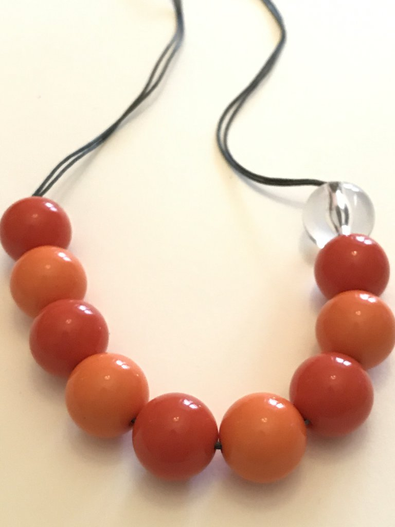 Collana lunga con perle colorate arancioni.