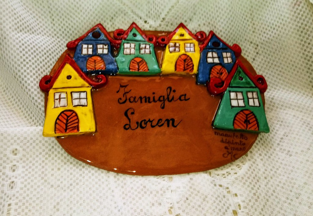 Placca da muro fuori porta di ceramica manufatta di forma ovale con case in rilievo con i loro particolari