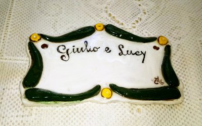 Targhetta fuori porta, manufatta di ceramica con cornice in rilievo con motivi verdi alternati a anellini gialli su fondo bianco