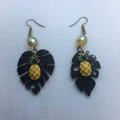Orecchini pendenti asimmetrici con foglie tropicali nere in resina e charms in ottone a forma di ananas e cristalli gialli