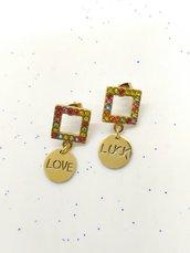 Orecchini pendenti realizzati a mano colore oro, zirconi colorati e ciondoli con scritte: LOVE & LUCK.