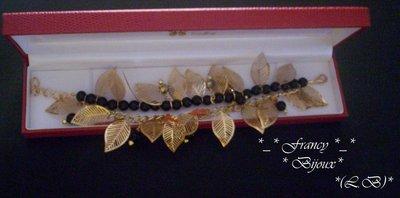 bracciale con foglie in metallo dorate e perle nere