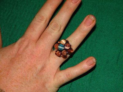 anello con fiorellone e spirali arancione e blu
