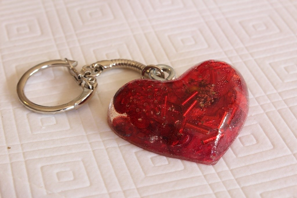 Portachiavi a forma di cuore in resina, con, all'interno, perline rosse