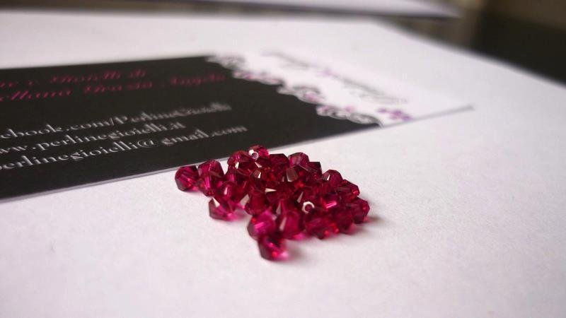 Swarovski® bicono 5301/5328, Ruby.  Diametro: 3 mm.