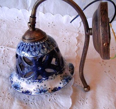 Applique-Lume campanella in ceramica con braccio in metallo anticato.
