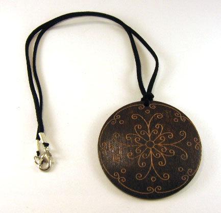 Collana con elemento in legno con incisioni floreali